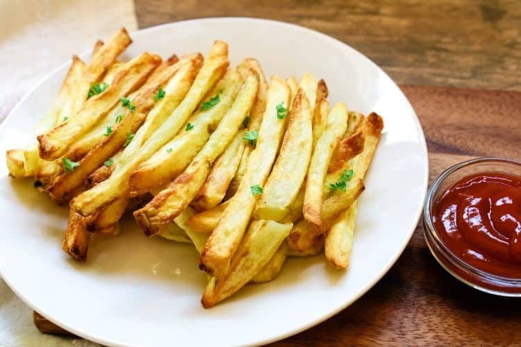 Air Fryer French Fries on white plate with small pinch bowl of ketchup