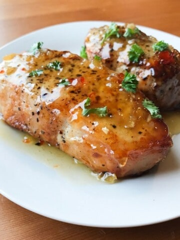 Air Fryer Pork Chops coated in honey garlic sauce on a white plate