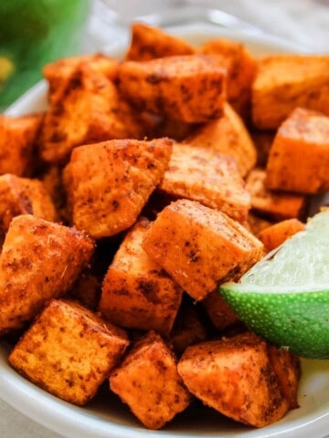 Air Fryer Mexican Sweet Potatoes in a white bowl with a lime corner showing