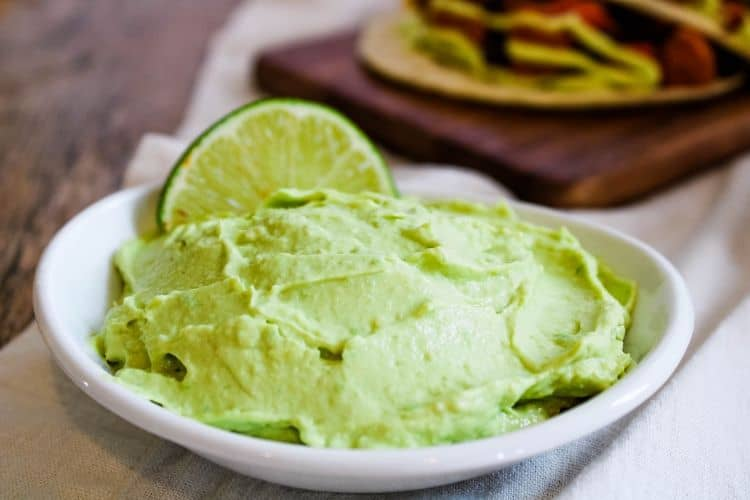 Avocado Lime Crema in white bowl with lime wedge