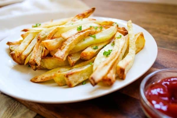 Crispy Air Fryer French Fries on white plate with ketchup on the side