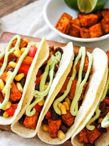 Sweet Potato Black Bean Tacos with white bowl of Mexican potatoes in background