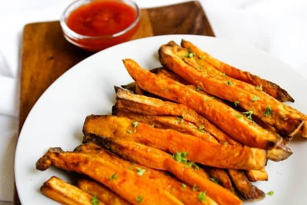 Air Fryer Sweet Potato Fries on a white plate with ketchup bowl in back