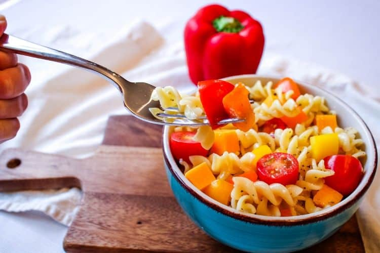 Fork in Italian Pasta Salad with with pepper in back