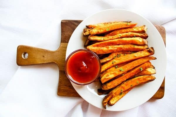 Sweet Potato Fries on white plate with ketchup on top of small bown cutting board