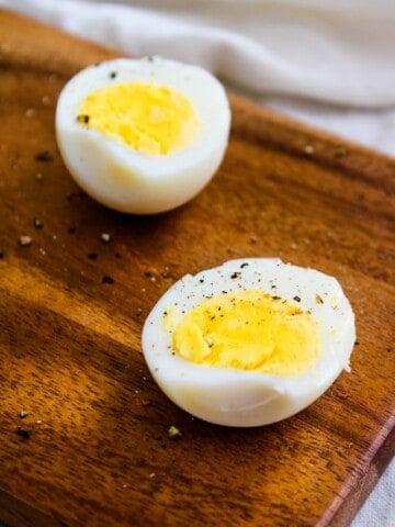Air Fryer Hard Boil Eggs on cutting board halved