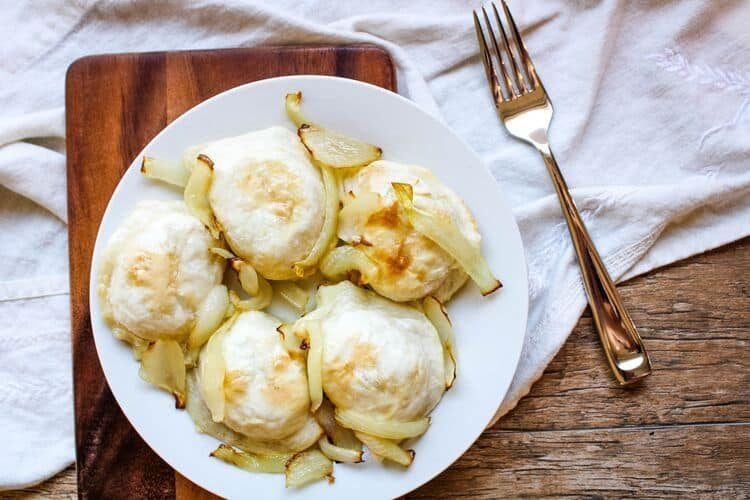Air Fryer Pierogies with onions on a white plate and fork to side