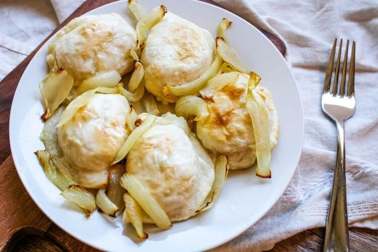 Air Fryer Pierogies from Frozen with onions on a white plate next to a fork