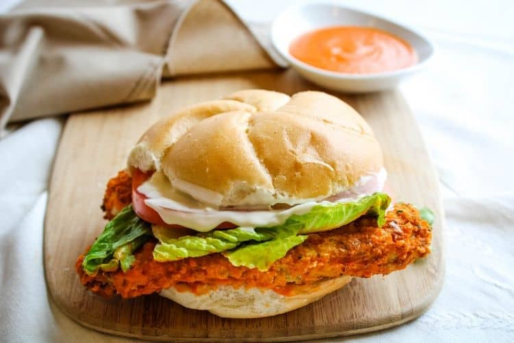 Buffalo Chicken Sandwich on cutting board with buffalo sauce in background