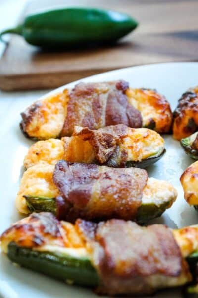 Air Fryer Bacon Jalapenos on a white plate with jalapeno pepper in background