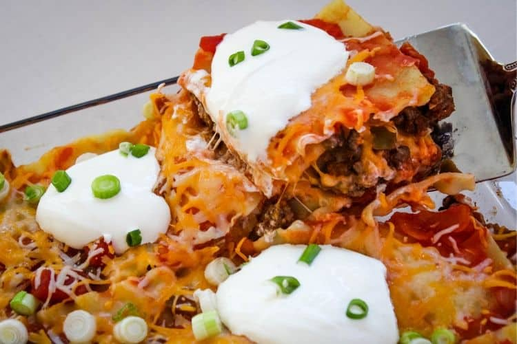 Taco Lasagna with slice being picked up in dish