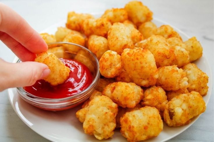 Air Fryer Tater Tots with one being dipped in ketchup