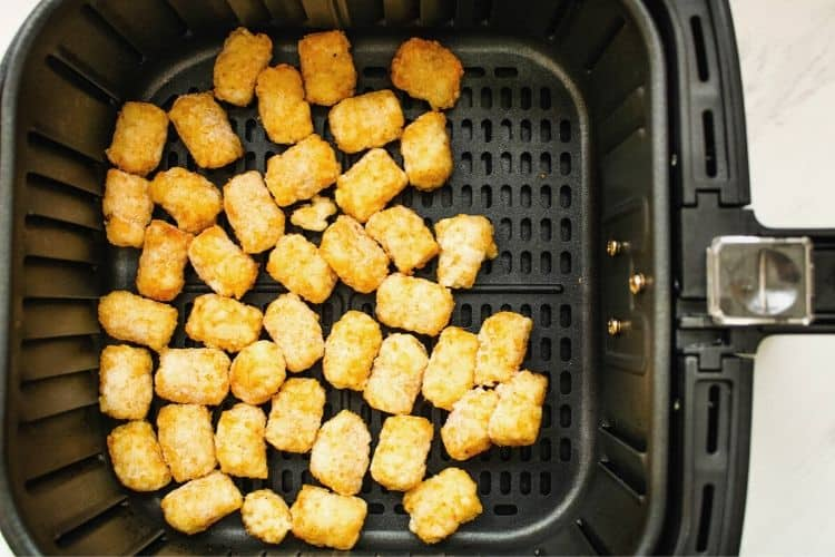 Tater Tots in air fryer basket from overhead view.