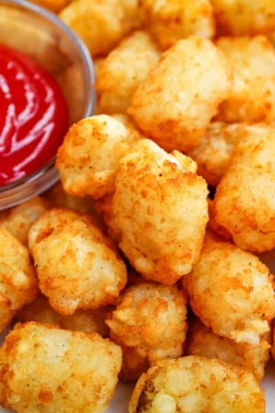 Closeup of Air Fryer Tater Tots with bowl of ketchup peaking into the top left