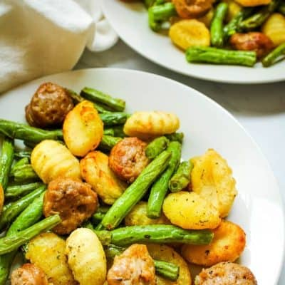 Sausage, Gnocchi, and Green Beans on a white plate