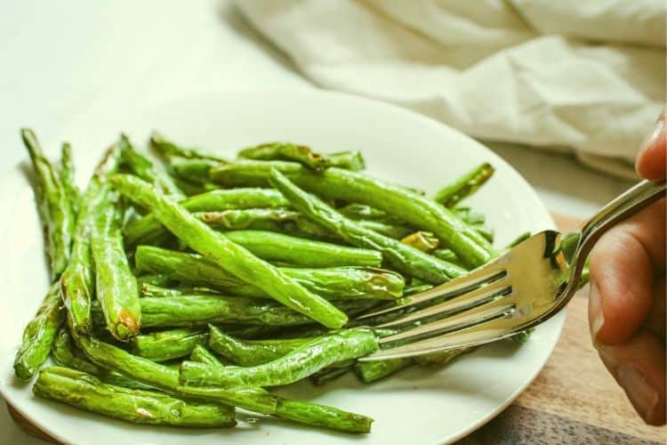 Air Fryer Green Beans on a white plate with fork in it