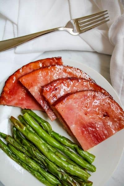 Ham Steaks with Green Beans on a white plate with fork over top of plate