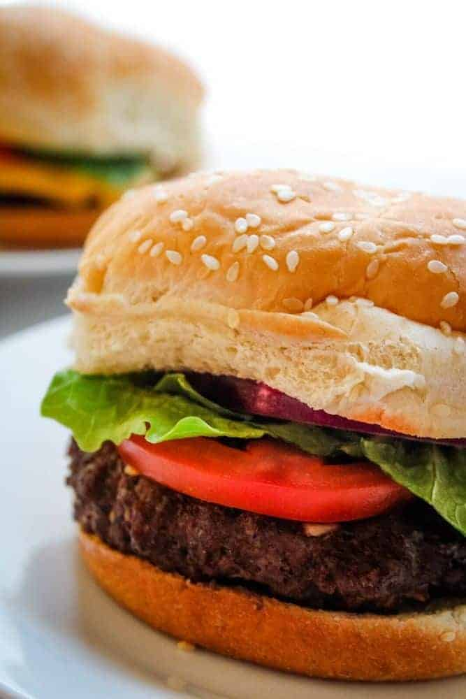 Closeup of Air Fryer Hamburger with lettuce and tomato on a sesame bun on a white plate