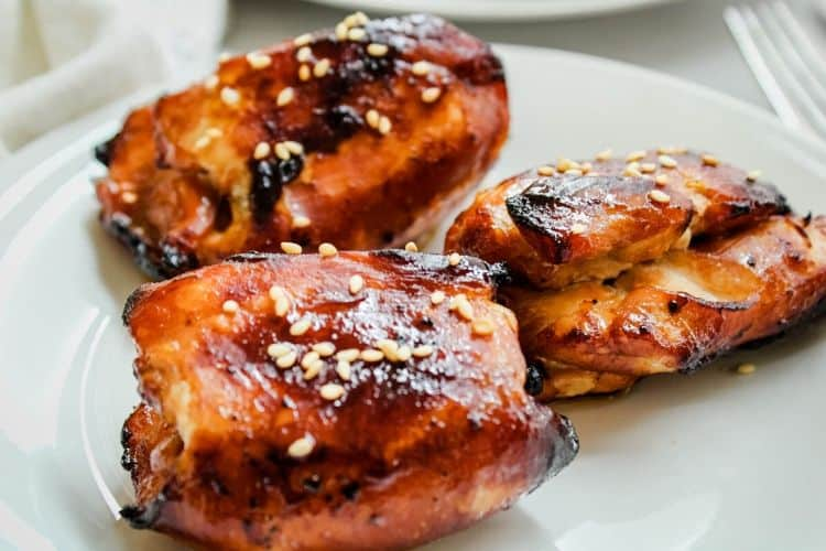 Honey Soy Air Fryer Chicken Thighs topped with sesame seeds on a white plate
