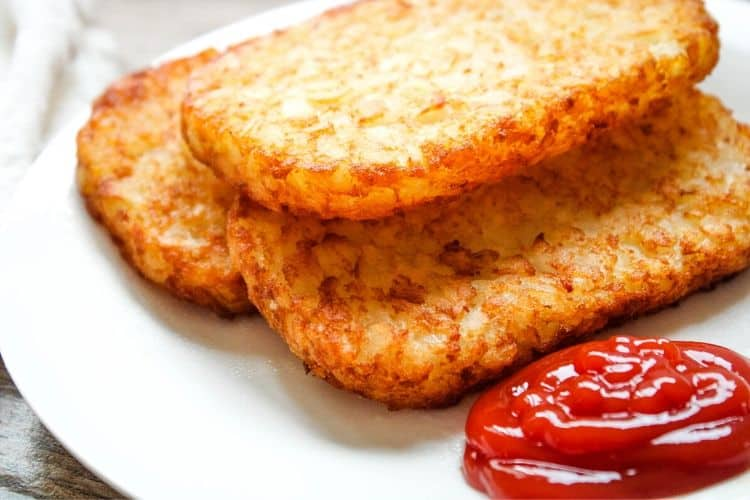 Crispy Hash Brown Patties on a white plate with ketchup