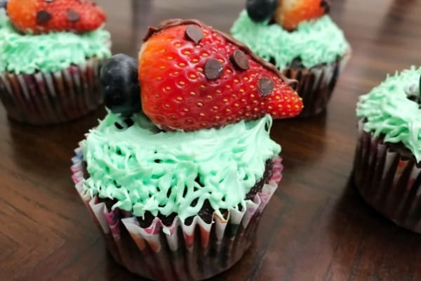 Chocolate Strawberry Ladybug Cupcakes on a brown table