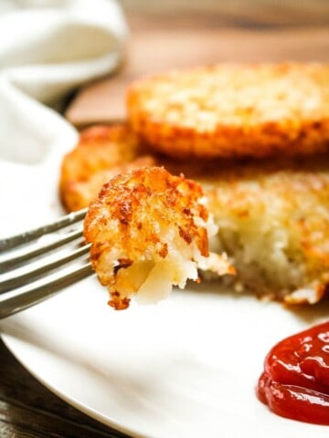 Closeup of a bite of crispy air fryer hash brown patties on a fork with ketchup to the side