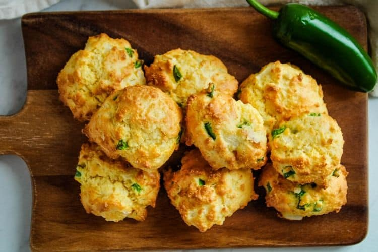 Hush puppies on cutting board with a jalapeno pepper in corner