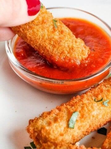 Dipping Mozzarella Stick in Marinara Sauce