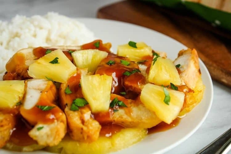 Chicken with Pineapple Sauce and Pineapple Chunks with rice on a white plate