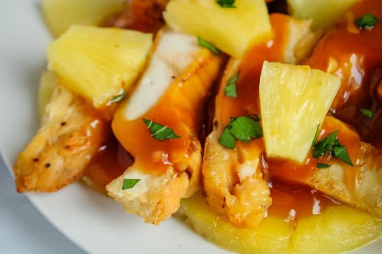 Closeup of Pineapple Chicken with pineapple chunks on a white plate