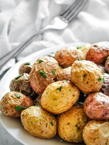 Air Fryer Baby Potatoes on a white plate with a fork in the background