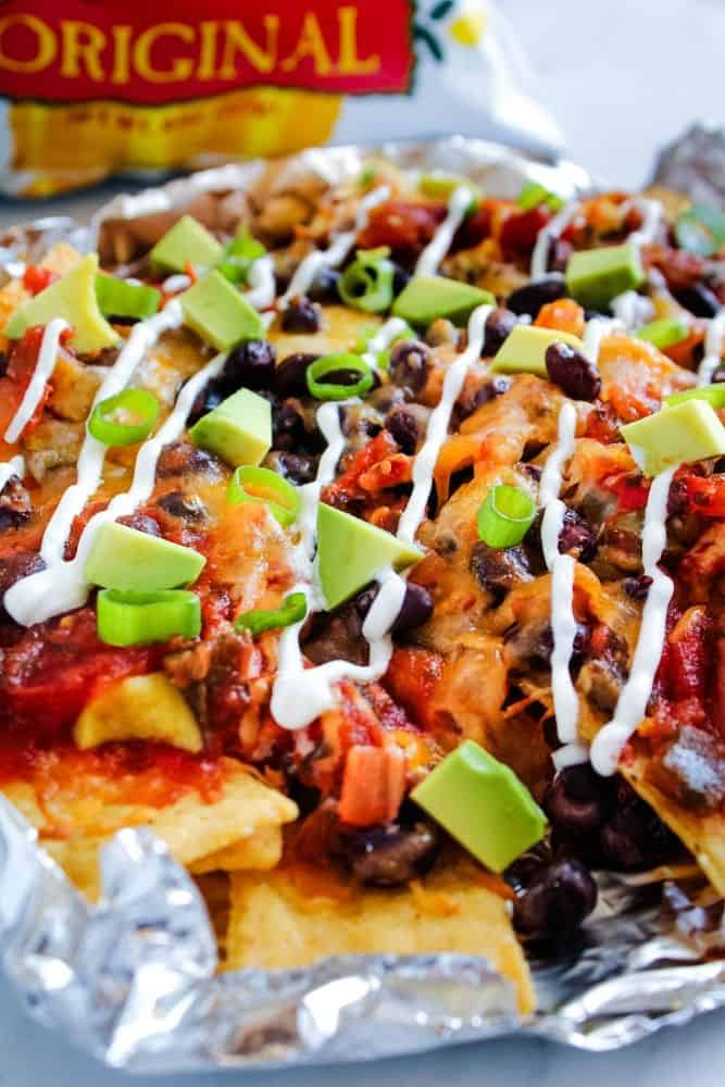 Air Fryer Nachos with beans, avocados, and sour cream on top