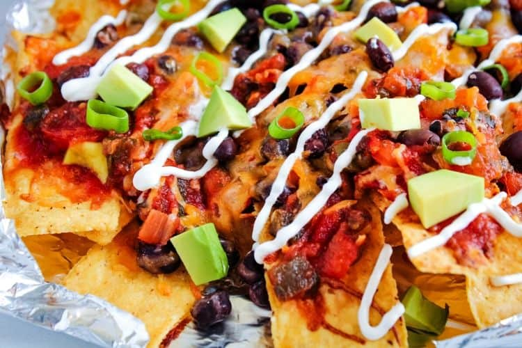 Closeup of air fryer nachos on aluminum foil and sour cream drizzled on top
