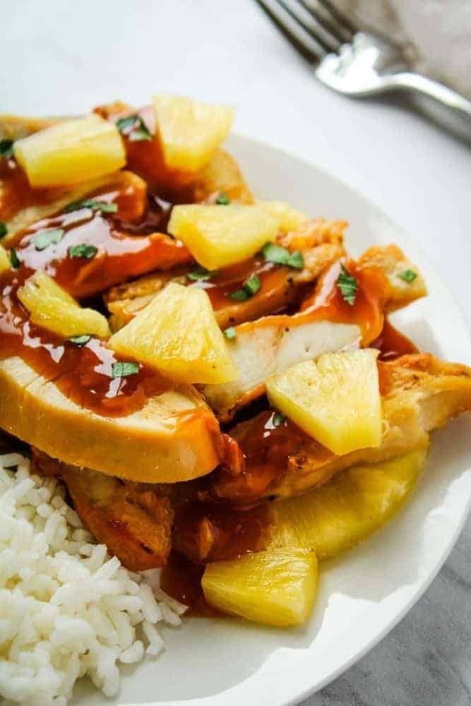 Pineapple Chicken with Pineapple Chunks and rice on a white plate
