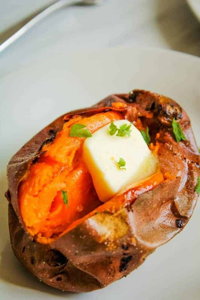 Air Fryer Baked Sweet Potato cut in half with butter in the middle