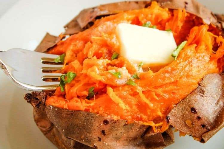 Air Fryer Baked Sweet Potato cut open and fluffed with butter and fork in the middle of it