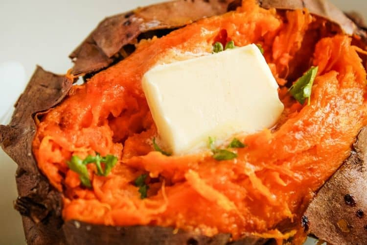 Closeup of baked sweet potato open on top with butter melting