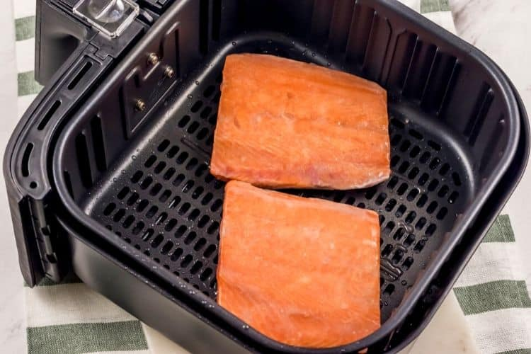 Raw salmon in an air fryer skin-side down.
