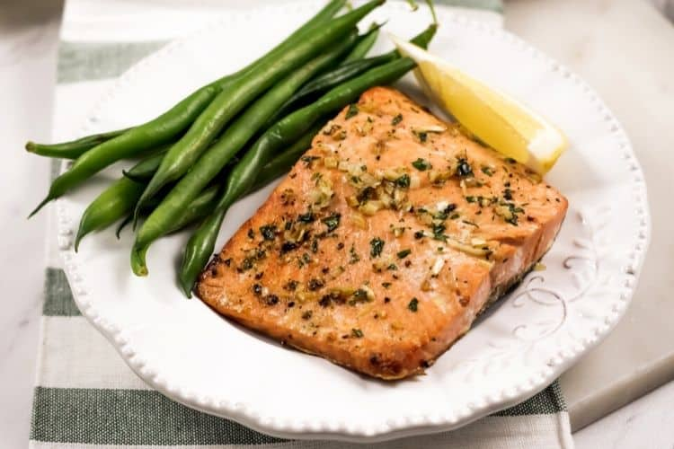 Garlic Salmon on a white plate with green beans and a lemon