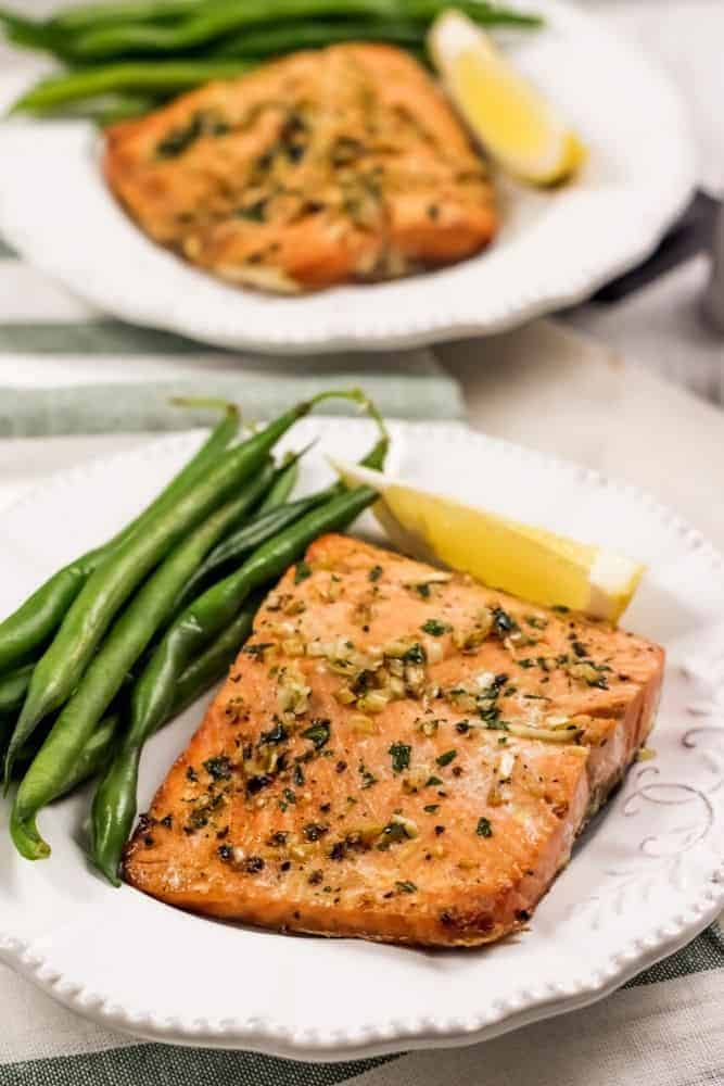 Vertical image of Air Fryer Garlic Salmon on a white plate with green beans and a lemon