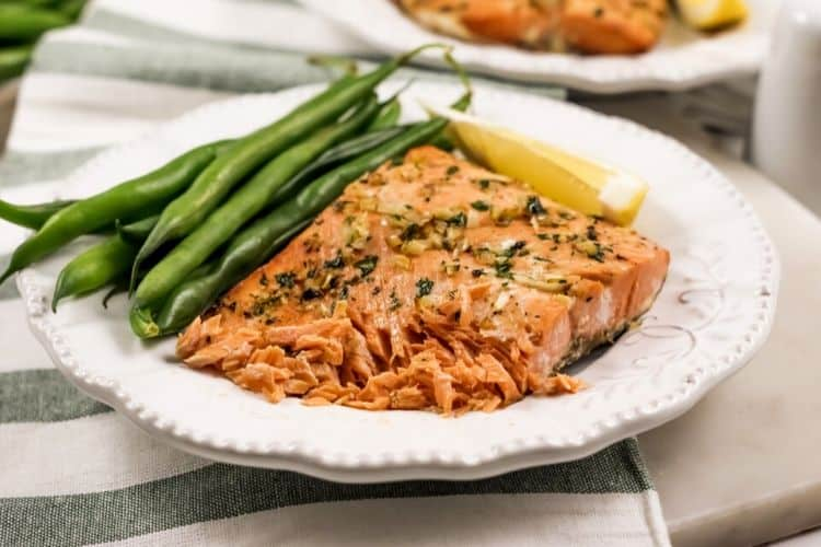Garlic Butter Salmon that is shown flaking on a white plate with green beans and a lemon