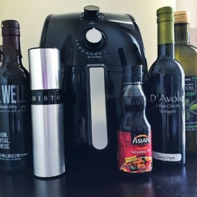Various oil containers in front of an air fryer.