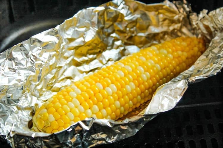 Cooked air fryer corn on the cob in foil opened up