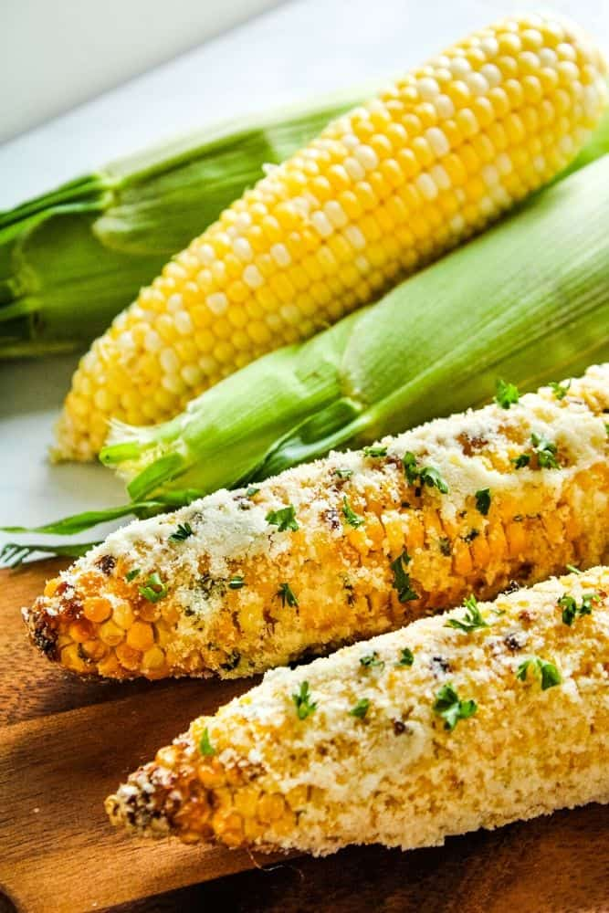 Air fryer corn on the cob with parmesan on a cutting board with more corn in the background
