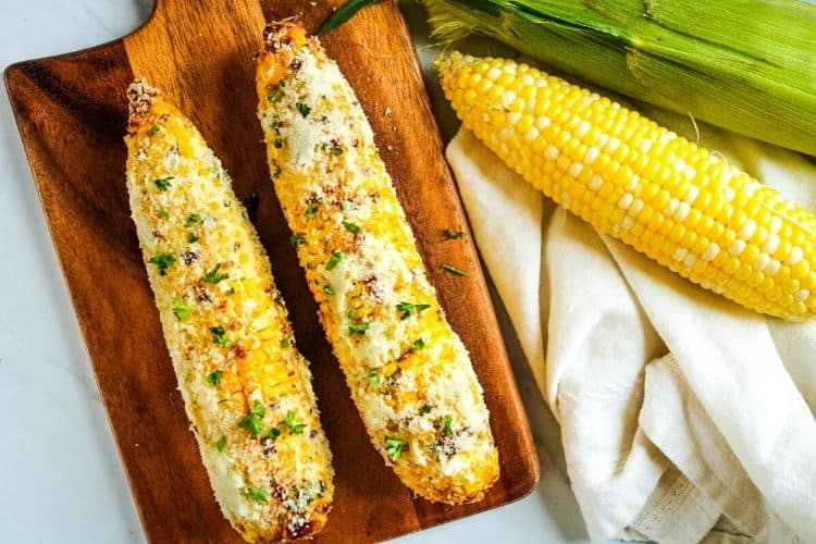 Air Fryer Corn on the Cob rolled in parmesan on a cutting board