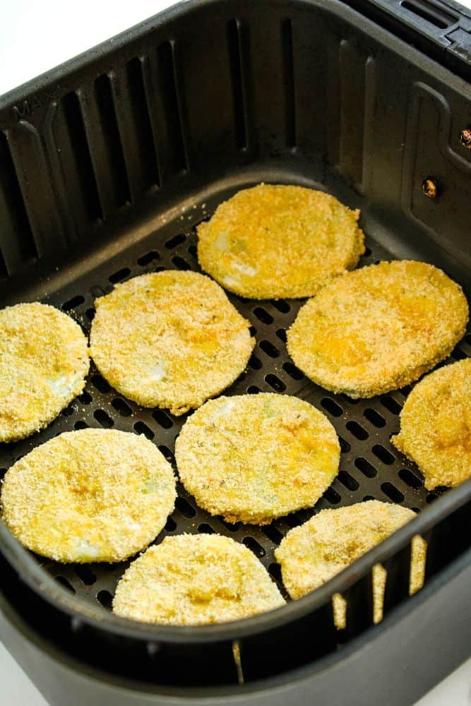 Breaded green tomato slices inside air fryer