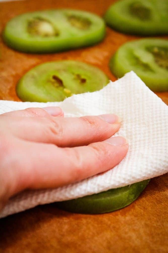 Using a paper towel to pat the green tomatoes dry