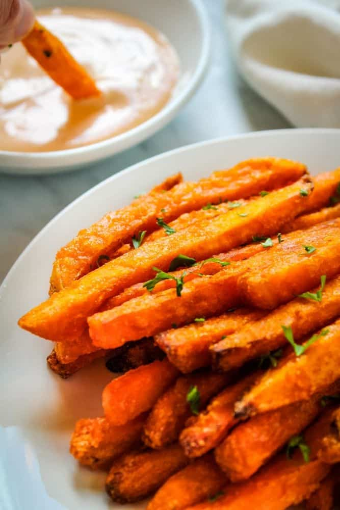 Air Fried Sweet Potato Fries on white plate with fry being dipped in sauce in background