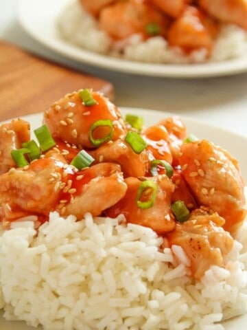 Air Fryer Sweet and Sour Chicken served over rice on a white plate