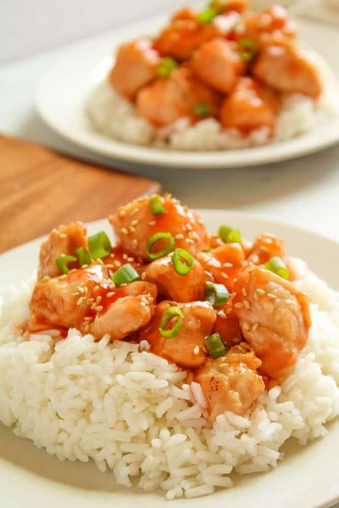 Air Fried Sweet and Sour Chicken with rice underneath on a white plate